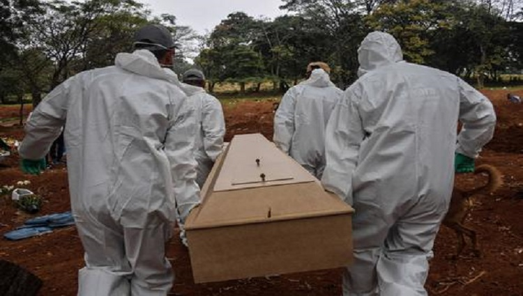 TOPSHOT - Employees carry the coffin of a person who died from COVID-19 at the Vila Formosa cemetery, in the outskirts of Sao Paulo, Brazil on May 20, 2020. - Brazil has emerged as the latest flashpoint in the coronavirus pandemic. The country has registered more than 270,000 cases and nearly 18,000 deaths so far, and the increase in infections is not expected to peak until June. (Photo by NELSON ALMEIDA / AFP)